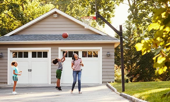 family playing basketball in front of two-car garage